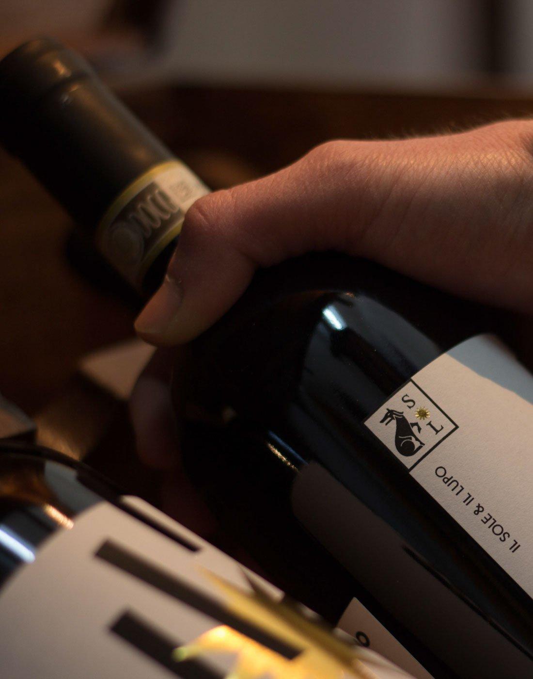 Scatto macro: una mano afferra una bottiglia di Lapiano